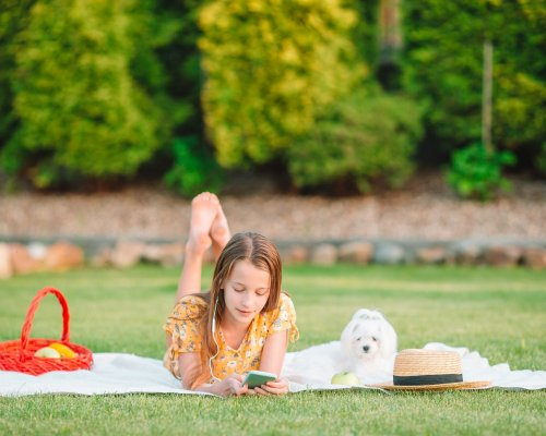 Beautiful little girl listen music and relax outdoors in the park