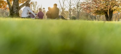 Young family sitting outdoors in the garden in autumn watching the setting sun in a low angle view over the green grass.